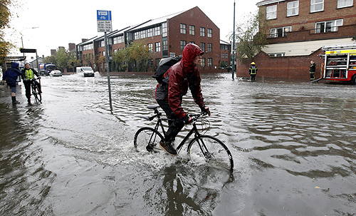 A commuter makes his way to work through flooded streets after torrential rain resulted in the major emergency plan being invoked in the County Dublin region, in Dublin.