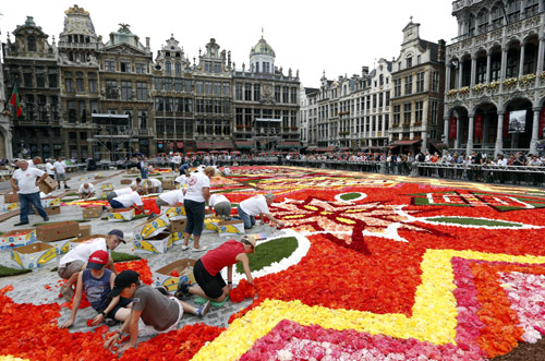Gardeners work on a giant carpet made of flowers to form a floral decoration at Brussels' Grand Place.