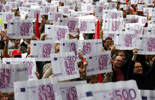 Demonstrators hold up large cardboard 500 euro notes and a sign reading fair sharing - taxes for the rich during an anti-capitalism protest in Frankfurt.