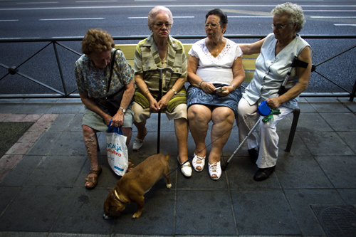 A group of women sit on a bench in the shade on a hot summer evening in Madrid.
