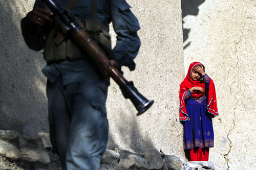 An Afghan girl watches as a member of the Afghan Uniformed Police walks past with paratroopers from Chosen Company of the 3rd Battalion (Airborne), 509th Infantry.