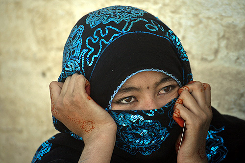 An Afghan woman with her hands decorated with henna sits while waiting to go back to Afghanistan from a United Nations (U.N.)-funded repatriation centre.