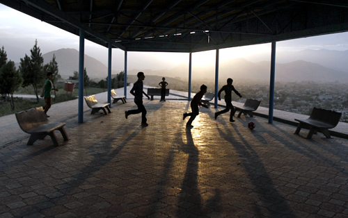 Afghan boys play football on a hill in Kabul.