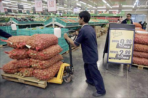 A worker pushes a cart of potatoes at a Metro cash-and-carry outlet in Kolkata.