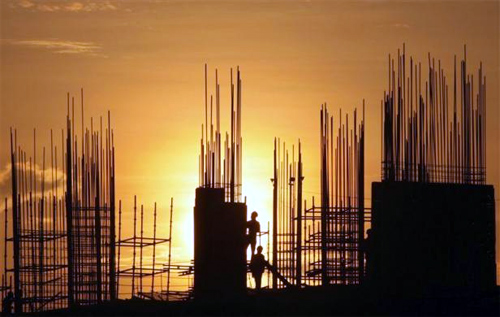 Image: Labourers are silhouetted against the setting sun as they work at the construction site of a residential building in Hyderabad.