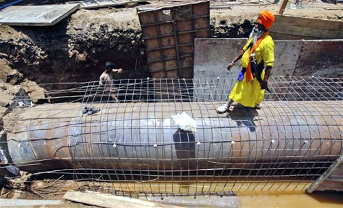 A man walks at the excavation site of a water pipeline in Mumbai.