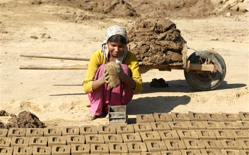 A woman labourer works in a brick factory at Libbar Hari in Uttarakhand.