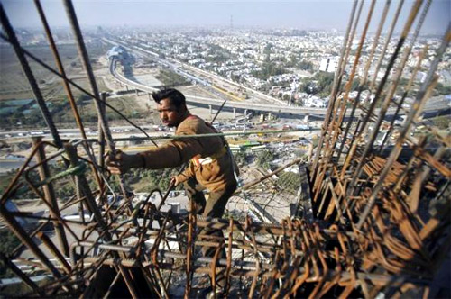 A labourer works at the construction of a residential complex at Noida in Uttar Pradesh.