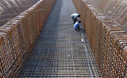 Labourers work at the construction site of a flyover on the outskirts of Ahmedabad.