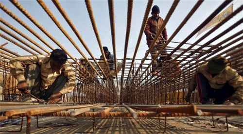 Labourers work on iron rods at the construction site of a flyover at Noida in Uttar Pradesh.