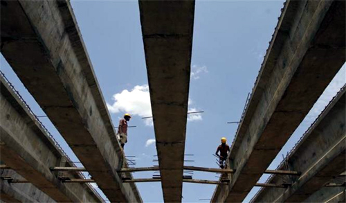 Workers stand at the construction site of a flyover bridge in Chennai.