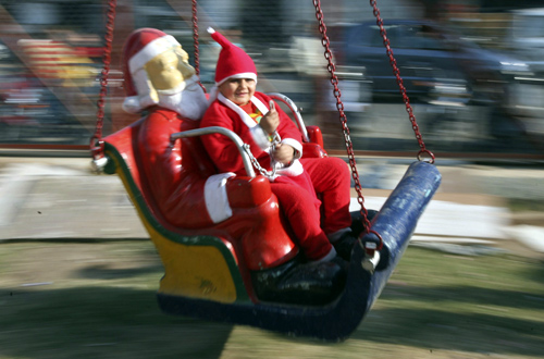 A boy dressed in a Santa Claus costume rides on a merry-go-round outside a church during Christmas celebrations in Jammu.