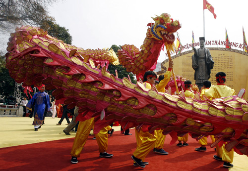 People perform the dragon dance in front of King Ly Thai To's statue.