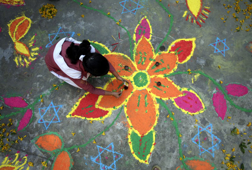 Students put the finishing touches to a rangoli, or a mural made out of coloured powders, at a school ahead of Diwali festival celebrations in Jammu.