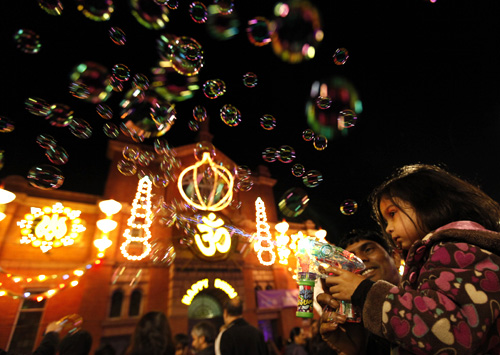 A girls shoots bubbles from a gun during the start of Diwali celebrations in Leicester, central England.