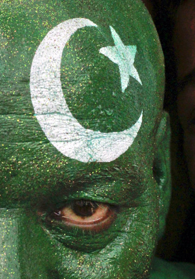A man with his face painted depicting the colours of the Pakistan national flag.