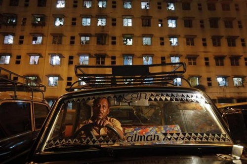 A driver waits for customers in front of an apartment building in his Premier Padmini taxi in Mumbai's suburbs.
