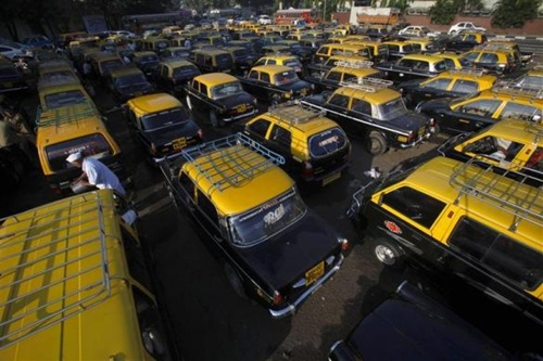 A driver stands amid parked taxis near Santa Cruz domestic airport in Mumbai.