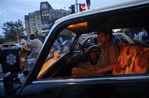 Vinay, 30, a taxi driver, looks out from his Premier Padmini taxi as he waits at a signal during rush hour in Mumbai.