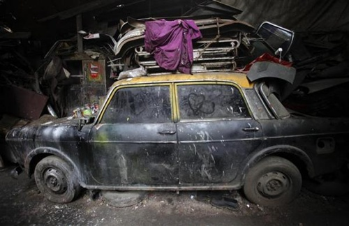 A de-registered Premier Padmini taxi is pictured covered in dust with love hearts etched on its windows inside a scrapyard in Mumbai.