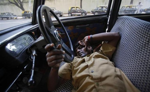 A taxi driver takes an afternoon nap with his hand on the steering wheel of his Premier Padmini taxi in Mumbai.