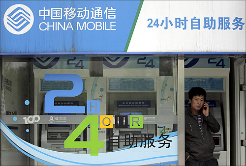 A man talks on his mobile phone at the entrance of a China Mobile booth in Beijing.