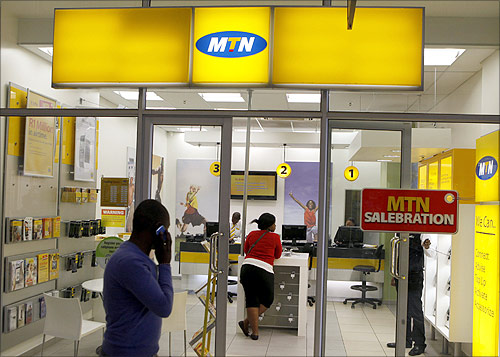 A man speaks on a mobile phone as he walks past a MTN shop at a shopping mall south of Johannesburg.