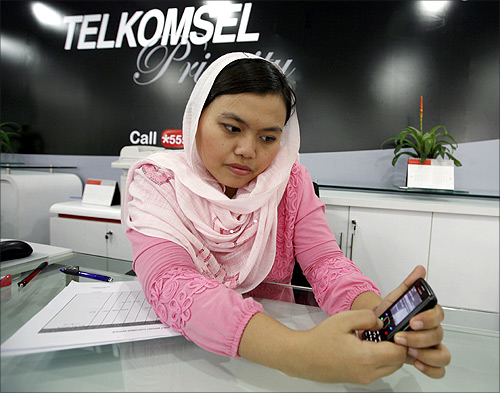 An employee of PT Telekomunikasi Satelit (Telkomsel) holds a customer's mobile phone at a service outlet in Jakarta.