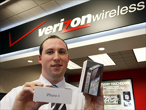 Chris Gates, assistant manager at a Verizon Wireless store, holds the new Verizon iPhones at his store in Boca Raton, Florida.