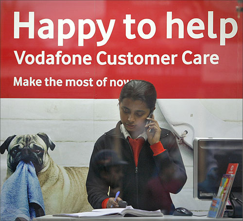 An employee talks on mobile phone inside a Vodafone store in Agartala.