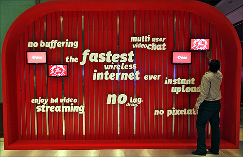 A man touches a screen on a Bharti Airtel advertisement billboard during the launch ceremony for 4G services in Kolkata.