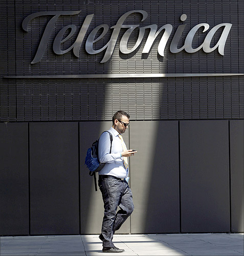 A man checks his phone outside Telefonica headquarters in Madrid.