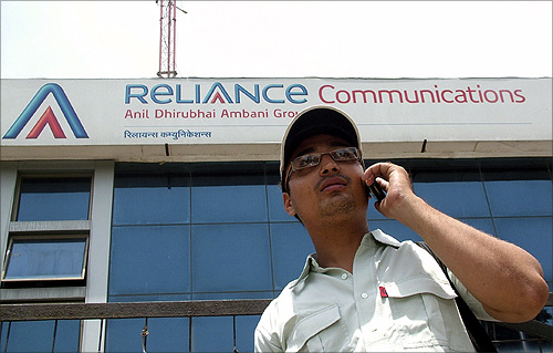 A man talks on a mobile phone in front of an advertisement for Reliance Communications in Mathura.
