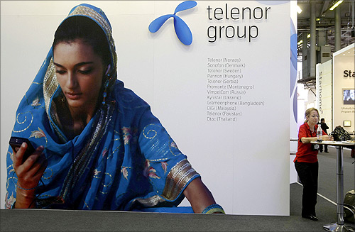 A visitor rests under a Telenor Group sign at the GSMA Mobile World Conference in Barcelona.