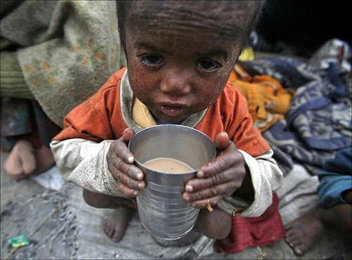 Three-year-old Babu, a child of a migrant labourer, holds a glass filled with tea outside a makeshift tent along a road on a cold morning in Noida in Uttar Pradesh.