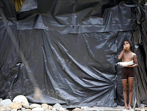 A child of a slum dweller eats food outside her house at a slum area in Jammu.