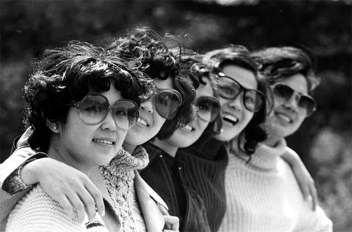 Women wearing sunglasses pose for a group photo at a park in Beijing in 1980.