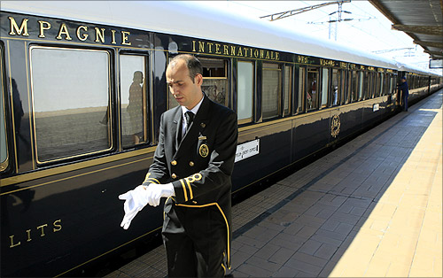 A car attendant puts on his gloves in front of the Orient Express at the main railway station in Bucharest September 3, 2012.