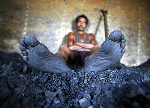 A labourer rests inside the wagon of a coal train as he takes a break from shovelling coal at a coal yard on the outskirts of Jammu.