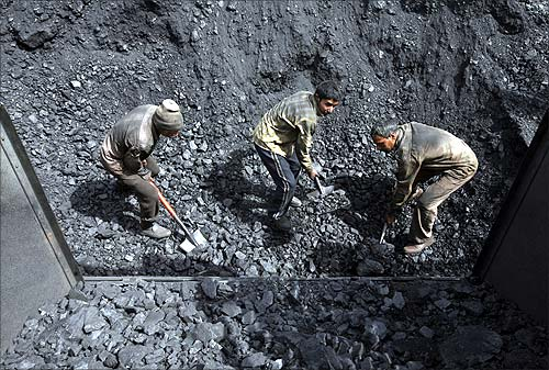 A worker shovels coal at a wholesale coal shop on the outskirts of Agartala.