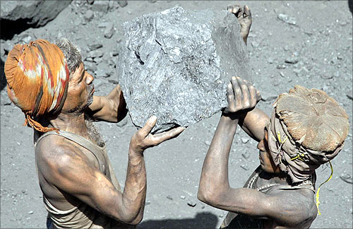 Labourers carry coal to load onto a truck at a coal yard on the outskirts of Allahabad.