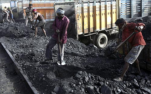 Labourers load coal onto trucks at Bari Brahamina, on the outskirts of Jammu.