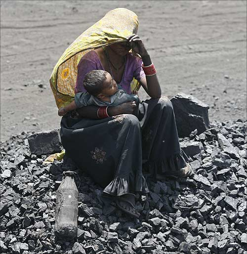 A woman labourer protects herself from sun as she holds her child at a coal yard on the outskirts of  Ahmedabad.