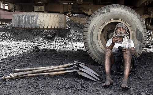 A labourer smokes after loading coal onto trucks at a coal yard near Chiwaki railway station in Allahabad.