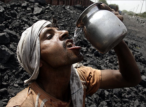 A labourer drinks water as he takes a break from loading coal onto trucks at a coal yard near Chiwaki railway station in Allahabad.
