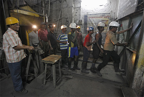 A worker opens the entry gate of an underground coal mine in the Mahanadi coal fields at Dera, near Talcher town in Orissa.