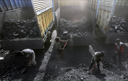 Labourers load coal onto trucks at a coal yard on the outskirts of Jammu.