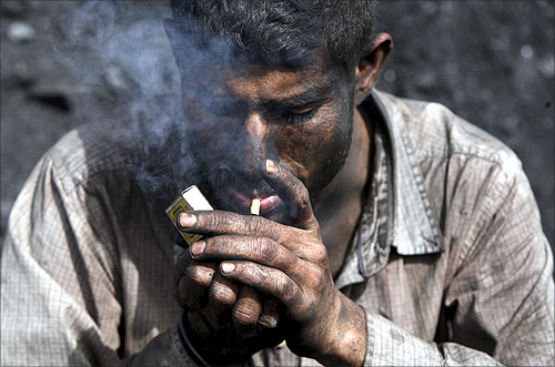 A labourer smokes a bidi, a local cigarette hand-rolled with tobacco leaf, during a break at a coal yard on the outskirts of Jammu.