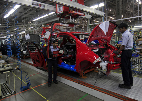 Employees work on a Chevrolet Beat car on an assembly line at the General Motors plant in Talegaon.