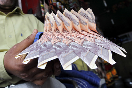 A Kashmiri shopkeeper staples together Indian currency notes to make a garland at a market in Srinagar.